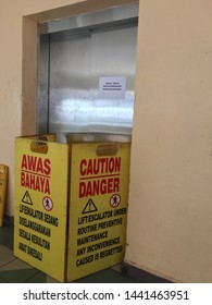 Melaka/Malaysia - July 4,2019 : Signage with Dual language text meaning CAUTION/ DANGER LIFT UNDER ROUTINE PREVENTIVE MAINTENANCE ANY INCONVENIENCE CAUSED IS REGRETTED