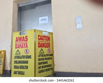 Melaka/Malaysia - July 4,2019 : Signange with Dual language text meaning CAUTION/ DANGER LIFT UNDER ROUTINE PREVENTIVE MAINTENANCE ANY INCONVENIENCE CAUSED IS REGRETTED