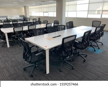 Melaka,November 2019:Interior of modern meeting room in office with long gray table with chairs & large potted plant.Windows with cityscape.The interior contains a certain grain or noise & soft focus