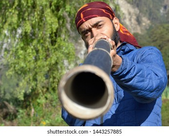 MELAMCHIGAON, HELAMBU / NEPAL - MAY 9, 2018: Young Indian traveller plays a didgeridoo in the Himalayas, on May 9, 2018.