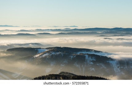 melancholic dreamy winter landscape with mountains and fog in the valleys early in the morning