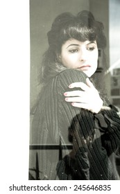 A melancholic, retro styled girl standing at the window.