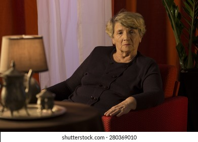 Melancholic senior lady relaxing alone in chair
