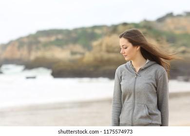 Melancholic teen looking down walking on the beach alone
