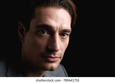 Melancholy. Close-up portrait of young attractive sad man is standing and looking at camera thoughtfully. Isolated on black background