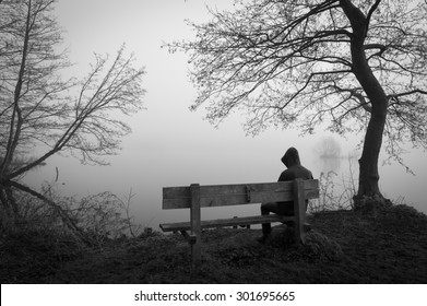 Melancholy emotions concept: sad man sitting on a bench at a foggy lake.