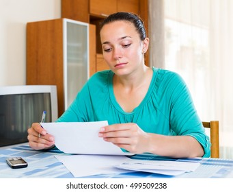 Melancholy girl working with documents at home