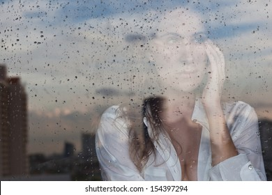 Melancholy reflection of the girl in the window
