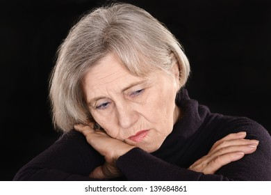 melancholy senior woman thinking on a black background