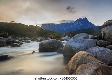 Melangkap River and rocky bottom Landscape scene with the majestic of Mount Kinabalu during sunrise. (Image has grain or blurry or noise and soft focus when view at full resolution.)