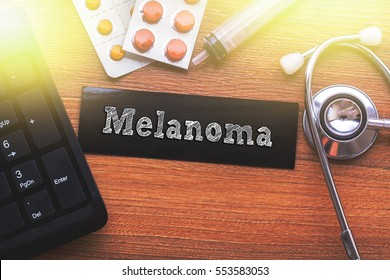 MELANOMA words written on label tag with medicine,syringe,keyboard and stethoscope with wood background,Medical Concept
