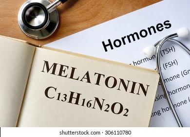 Melatonin  word written on the book and hormones list.