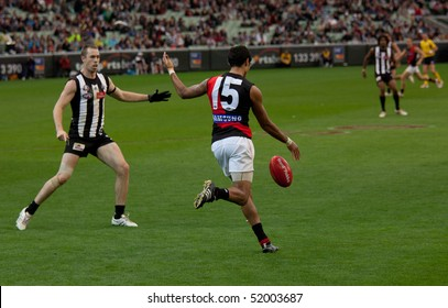 MELBOURNE - APRIL 25: Essendon's Courtney Dempsey kicks while Collinwood captain Nick Maxwell stands the mark in Collingwood's massive win over Essendon - April 25, 2010 in Melbourne, Australia.