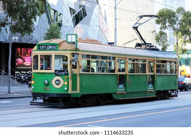 Melbourne, AU - MAY 13, 2018: The old vintage green-yellow tram is running on the CBD Free Tram of City Circle Line, for sending tourists to Flinders St. station.