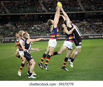 MELBOURNE - AUGUST 21:  Adelaide's Scott Stevens (centre) and Collingwood's Chris Dawes (r) stretch for a mark during Collingwood's win over Adelaide - August 21, 2010 in Melbourne, Australia