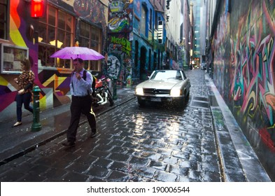 MELBOURNE, AUS - APR 10 2014: Pedestrians and a car pass at Hosier Lane.Hosier lane is a much celebrated landmark in Melbourne mainly due to its sophisticated graffiti urban art.
