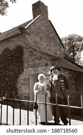 MELBOURNE, AUS - APR 14 2014:Couple wearing English costumes from the 17th century era at Captain Cooks Cottage.It's a popular tourist attraction located in the Fitzroy Gardens, Melbourne, Australia.