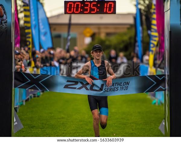 MELBOURNE, AUSTRALIA -02 FEBRUARY, 2020: 2XU Triathlon Series, Elwood Beach, Melbourne 2020, Race 4, Winner of Fun Tri event crossing the finish line.