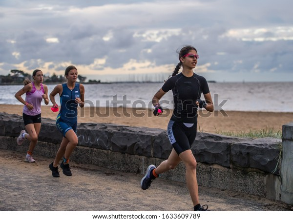 MELBOURNE, AUSTRALIA -02 FEBRUARY, 2020: 2XU Triathlon Series, Elwood Beach, Melbourne 2020, Race 4, Female youth Fun Tri section of the event. Running along the beach.