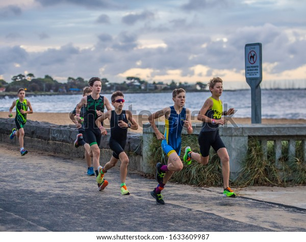 MELBOURNE, AUSTRALIA -02 FEBRUARY, 2020: 2XU Triathlon Series, Elwood Beach, Melbourne 2020, Race 4, Male youth Fun Tri event running along the beach.