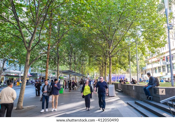 MELBOURNE, AUSTRALIA - APR 12: People walking on foot path of Swanston Street full of trees in Melbourne City on Apr 12, 2016. Melbourne the world's most liveable city for the fifth year running
