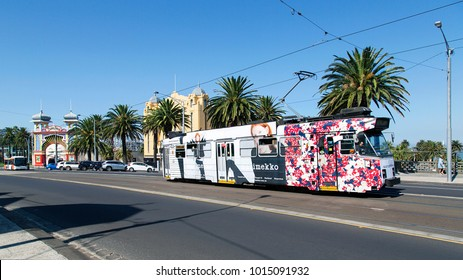 Melbourne, Australia: April 04, 2017: A tram leaves Acland Street and travels past Luna Park in St Kilda towards the city centre. The public transport system runs through all the major suburbs in Melb