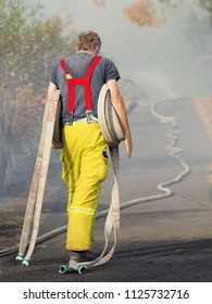 Melbourne, Australia - April 13, 2018: Fire fighter with rolls of fire hose at a bush fire in an suburban area of Knox City in Melbourne east.