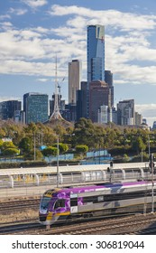 Melbourne, Australia - August 15, 2015: V-line train leaving downtown Melbourne with iconic buildings in the background
