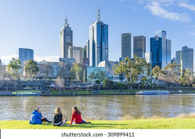 Melbourne, Australia - August 15, 2015: People sitting on Banks of Yarra River in Melbourne near sunset with cityscape as the background.