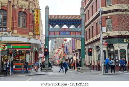 Melbourne, Australia - August 15, 2018: People gather by the Chinatown gate in the city centre. Chinese migrants first settled in the area in 1800s, since becoming a major tourist attraction.