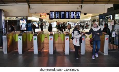 Melbourne, Australia - August 22, 2018: Rail passengers pass through ticket barrier turnstile gates at Flinders Street Railway Station in the city centre.