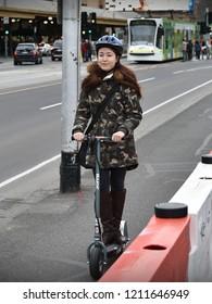 Melbourne, Australia - August 22, 2018: A woman rides an electric scooter along a city centre road.