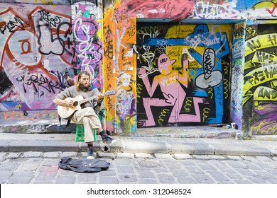 Melbourne, Australia - August 30, 2015: Street musician playing guitar in Hosier Lane in Melbourne. Hosier Lane is one of the city's best street art locations.