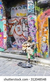 Melbourne, Australia - August 30, 2015: Street musician playing guitar in Hosier Lane in Melbourne. Hosier Lane is one of the city's best street art locations.