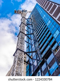 Melbourne, Australia, city office building under construction with a large crane against a blue sky with white clouds.