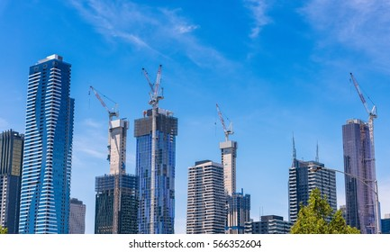 Melbourne, Australia, city skyline with many buildings under construction against a blue sky with light clouds.