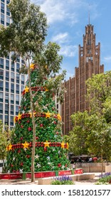 Melbourne, Australia - December 16, 2009: Giant artificial Christmas tree composed by green, red and green stars with Manchester Unity building tower in back. All under blue cloudscape.