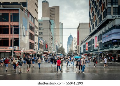 Melbourne, Australia - December 27, 2016: People crossing the intersection of Elizabeth and Flinders street in Melbourne City Business District on a rainy summer day.