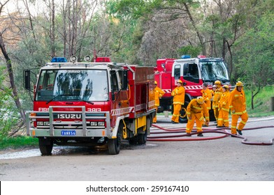 MELBOURNE, AUSTRALIA - February 10, 2015: Volunteer fire fighters from the North Warrandyte brigade of the Country Fire Authority practicing by the Yarra River in Warrandyte, with Isuzu fire trucks.