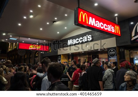 Melbourne, Australia - February 21, 2016: people crowding the footpath on Swanston Street outside McDonald's during the White Night arts festival. In Australia many McDonald's are branded Macca's.