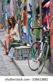 MELBOURNE, AUSTRALIA - FEBRUARY 27, 2015. Street view at Hosier Lane in Melbourne, with lady checking her smartphone, bicycle and colored walls.