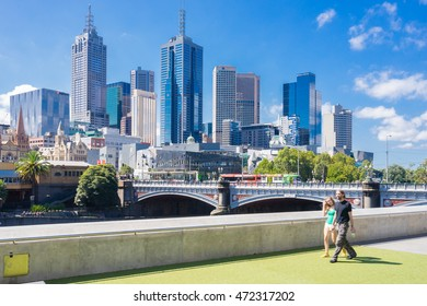 Melbourne, Australia - February 27, 2016: Tourists walking with Melbourne skyline as the background during daytime. Melbourne is ranked the world's most liveable city in sixth consecutive years.