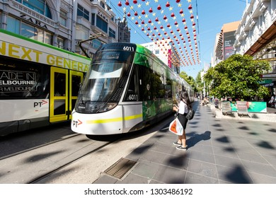 Melbourne, Australia - January 8, 2019: A person standing in front of two trams passing by at Bourke Street Mall.
