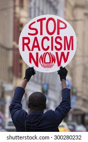 Melbourne, Australia - Jul 25, 2015: Protester holding a stop racism now placard outside Flinders Street Station in Melbourne, Australia