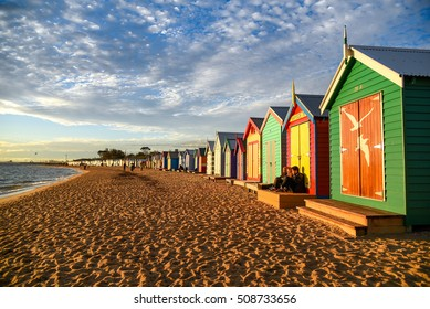 MELBOURNE, AUSTRALIA - JULY 18, 2016 : Tourists sit on deck of bathing boxes at Brighton Beach near Melbourne, Australia.
