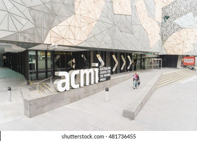 Melbourne, Australia - July 29, 2016: A man walking pass the Australian Centre for the Moving Image in Federation Square, Melbourne. The centre promotes film and digital media to the public.