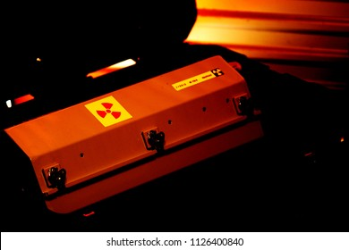 Melbourne, Australia - June 20, 2018: Box shaped metal container with radiation warning in a military grade transport box under red light