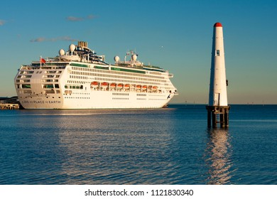 Melbourne, Australia - June 6 2018: A lighthouse and white transatlantic liner on the background of a  beautiful calm ocean without waves with a slight rippling. Port of Melbourne, Australia.