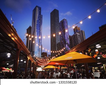 Melbourne, Australia: March 06, 2019: Melbourne's famous Summer Night Market selling only ethnic food and drink - every Wednesday at Victoria Market. Melbourne Cityscape background.