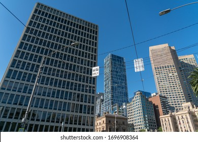 Melbourne Australia - March 10 2020; Department of Treasury and Finance with passing flanked by other city buildings viewed through tram powerlines from low point of view.
